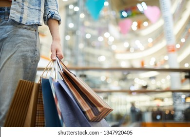 Close-up of unknown woman in jeans carrying shopping bags in mall, she doing shopping alone
