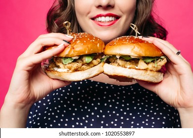 Close-up of unrecognizable brunette smiling woman holding two delicious fresh burgers with juicy roasted chicken and rocket salad.