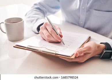 Close-up of unrecognizable businessman sitting at table with tea mug and making notes in application form