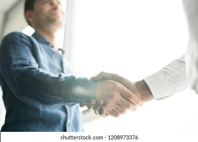 Close-up of unrecognizable businessmen starting new business collaboration and shaking hands against window