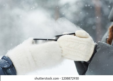 Close-up of unrecognizable campers in white mittens holding thermos mugs and toasting with hot drink in winter, they standing under snow