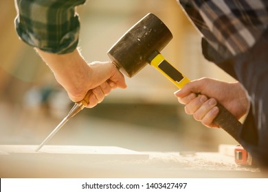 Closeup of unrecognizable carpenter hitting nail with hammer while working in joinery, copy space