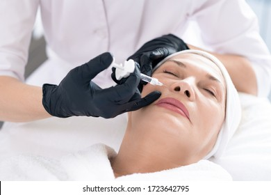 Close-up of unrecognizable cosmetologist using syringe while injecting filler in womens face to rejuvenate her skin