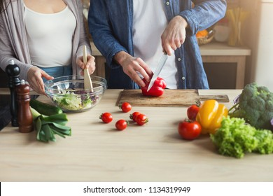 Closeup of unrecognizable couple cooking healthy food together in their loft kitchen at home. Cutting vegetables, preparing vegetarian salad, copy space