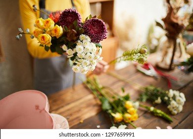Closeup of unrecognizable florist arranging bouquets in cozy flower shop, copy space