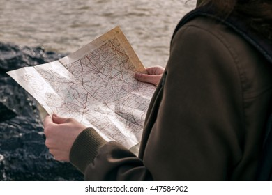 Close-up of unrecognizable girl holding map in sunlight