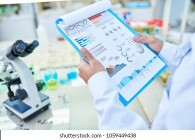 Close-up of unrecognizable laboratory worker viewing statistical data while analyzing result of DNA test