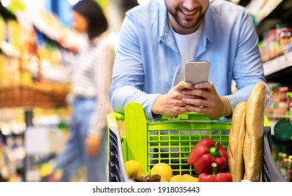 Closeup Of Unrecognizable Man Using Mobile Coupon App For Groceries Shopping Buying Food In Supermarket, Standing With Cart In Hypermarket. Smiling Guy Using Smartphone Purchasing Grocery In Shop