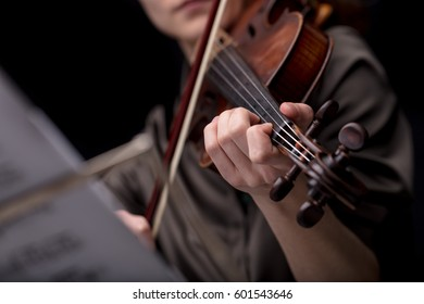 closeup of an unrecognizable musical player's hand holding a violin while playing it. Portrait on a black room with music score blurred in foreground