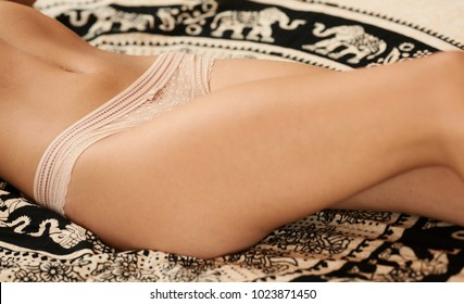 Close-up of unrecognizable slim girl in lace thong lying on black and white patterned blanket on bed.