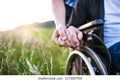 A close-up of unrecognizable son holding his father's hand on a wheelchair.