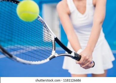 Closeup of unrecognizable tennis player hitting ball with racket while playing sports in indoor court, copy space