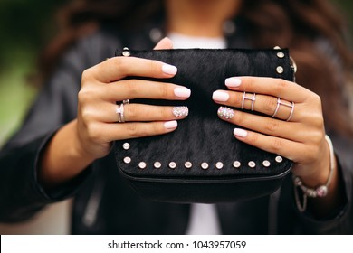 Close-up of unrecognizable woman with beautiful trendy manicure wearing wedding set and jewelry holding small black fancy handbag.