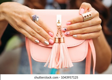 Close-up of unrecognizable woman with fashionable manicure of golden and pink colors with picture wearing trendy rings holding small peach or pink crossbag with tassel.