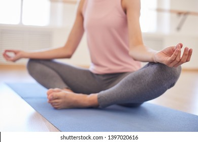 Close-up of unrecognizable woman in gray leggings sitting in butterfly pose and keeping hands in mudra while keeping calm at yoga