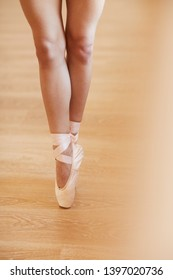 Close-up of unrecognizable woman in pointe shoes standing on tiptoes while performing ballet at rehearsal