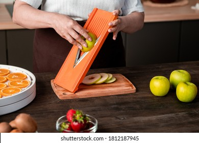 Close-up of unrecognizable woman using mandoline slicer for cutting apple while preparing fruits for dehydration at home - Shutterstock ID 1812187945