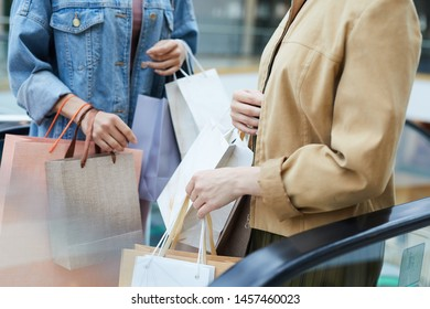 Close-up unrecognizable women with many shopping bags standing on escalator and chatting