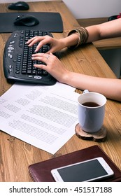 Close-up of unrecognizable young businesswoman using keyboard with documents and coffee in cup on table.