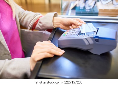 Closeup of unrecognizable young woman paying via credit card using NFC technology in shopping mall or cafe, copy space