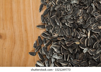 Closeup of unshelled sunflower seeds on wooden background. Organic snack