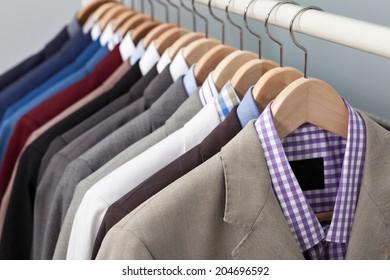 Nahaufnahme des oberen Teils einer Reihe von verschiedenen farbigen Anzügen in einem Kleiderschrank auf Hängen in einem Laden oder Showroom