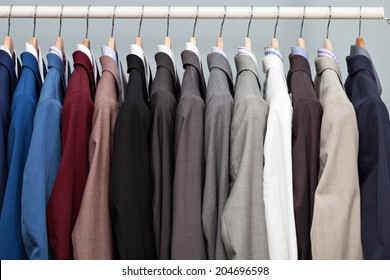 Closeup of the upper section of a row of different coloured man suits in a closet on hangers in a store or showroom