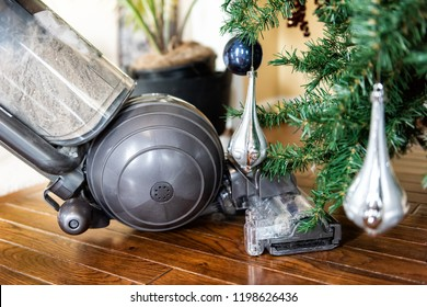 Closeup of upright vacuum cleaner head cleaning, vacuuming under Christmas Tree needles with New Years ornaments on hardwood wooden floor