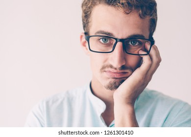 Closeup of upset annoyed blonde guy with disgusted face. Bored young Caucasian man in glasses leaning chin on hand. Boredom concept
