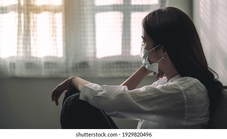 Close-up of an upset Asian patient woman wearing a face mask at home or hospital alone on a sofa waiting for a doctor. Hospital and Health care during Coronavirus or Covid-19 quarantine concept.