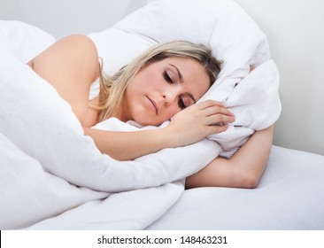 Close-up of upset woman lying on bed