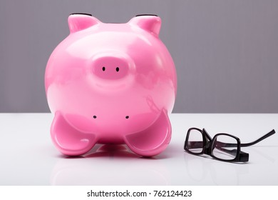 Close-up Of Upside Down Piggy Bank On Table With Eye Glasses On Desk