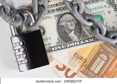 Closeup of US Dollar and European Union Euro banknotes under metallic chain and black combination padlock. Financial safety, currencies, money protection, fiat money and fiscal policy concepts