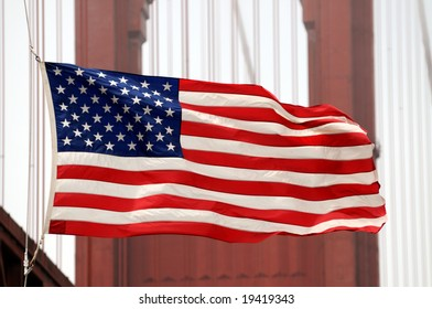 Closeup of U.S. flag in front of the Golden Gate Bridge in San Francisco