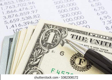 Closeup US money dollar with black modern pen put on income annual reports. Concepts of accounting, audit, tax return and budget fund.