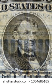 Close-up at US president Lincolns's face, highly magnified surface of used 5 dollars note with visible details of cotton fiber paper, with all flaws, watermarks and traces of usage.