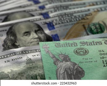 Close-up of USA tax return check and hundred dollar banknotes