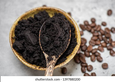 closeup used coffee grounds in wooden spoon