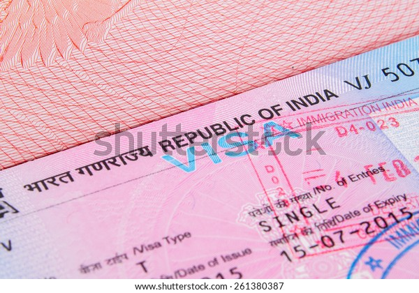 A closeup of used Indian tourist visa vignette inside a passport. Shallow DoF with focus on the word VISA single with immigration stamp  macro