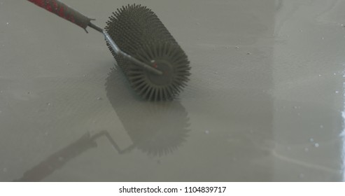 closeup using spike roller to remove air bubbles from self leveling floor