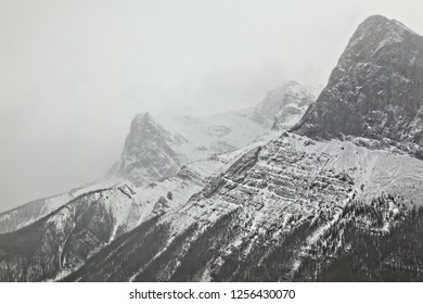 Close-up using a telephoto lens zooming on the summit of the Three Sisters Mountain range during snow storm in the Canadian Rocky Mountain in Canmore Alberta