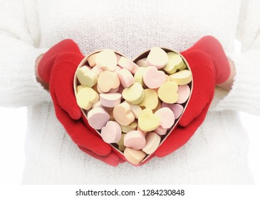 Closeup of a Valentines Day heart shaped box filled with candy hearts. Vignette added as unrecognizable woman holds the box in front of her torso.