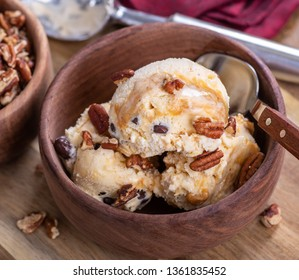 Closeup of vanilla caramel ice cream with pecans in a wooden bowl