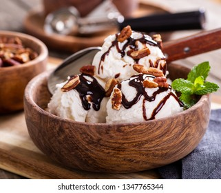 Closeup of vanilla ice cream topped with chocolate syrup and pecans in a wooden bowl