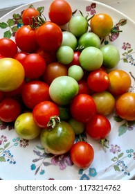 Closeup of a variety of green, red and orange tomatoes on a plate.