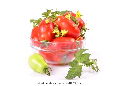 close-up of a variety red tomatoes in a bowl, green leaf