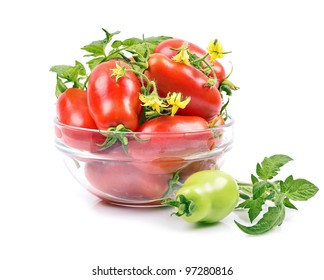 close-up of a variety ripened red tomatoes in a bowl, green leaf isolated white background
