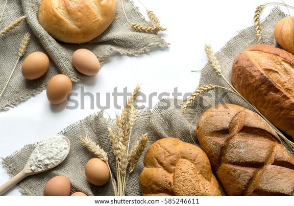 Closeup of various bread, sheaf of wheat, spoon filled flour and eggs on linen texture, isolated on white