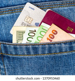 Closeup of various countries hundred banknotes, EU passport and contactless credit card peeking out of blue jeans back pocket. Luxury travel or shopping, good earnings, emigration concept.