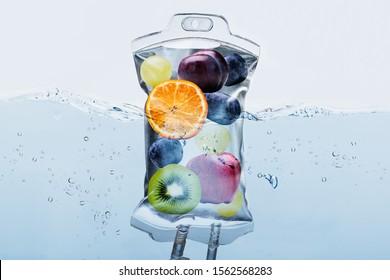 Nahaufnahme verschiedener Fruchtscheiben in Salzbeutel Einbruch in Wasser auf weißem Hintergrund